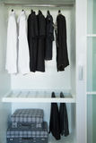 Clothes hang on a shelf in a designer clothes store, modern closet with row of cloths hanging in wardrobe, vintage rooms Stock Photos