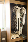 Clothes hang on a shelf in a designer clothes store, modern closet with row of cloths hanging in wardrobe, vintage rooms Stock Images