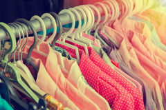 Clothes hang on a shelf in a designer clothes store in retro col Royalty Free Stock Photography