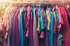 Clothes hang on a shelf in a designer clothes store in retro col Stock Photo