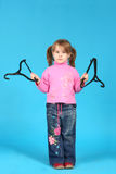 Clothes hanger. Child keeps clothes hanger, blue background Royalty Free Stock Images