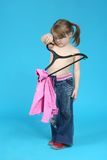 Clothes hanger. Child keeps clothes hanger, blue background Royalty Free Stock Photo