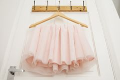 Clothes hanger with pink girl tutu dress isolated on the white door. Fashion, baby clothes. Clothes hanger with pink girl tutu dress isolated on the white door royalty free stock image