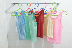 Clothes hanger with sleeveless children`s shirt Stock Photo
