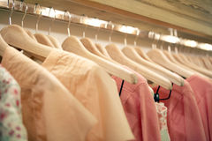 Clothes on Hangers. Detail of pink clothes hanging on wooden hangers in a fashion store Royalty Free Stock Image
