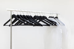 Clothes hangers and bags are on rod, white background Royalty Free Stock Photos