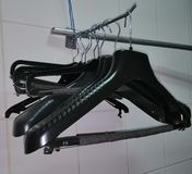Clothes hangers in black, hang empty on iron hardware stock photography