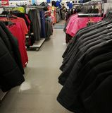 Sports clothing store shelving with clothes royalty free stock photos