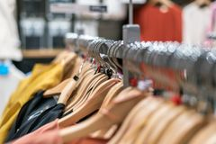 Clothes on hangers on racks in mass market.  Royalty Free Stock Photos