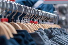 Clothes on hangers on racks in mass market.  Royalty Free Stock Photography