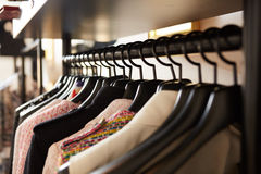 Clothes on hangers in shop. Close up. Shallow dof Royalty Free Stock Photography