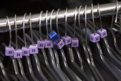 Clothes hangers with sizes. Hangers for clothes with size label cubes on a chrome rail Stock Photos