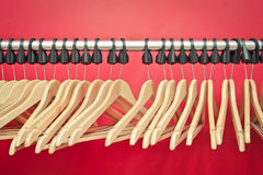 Clothes hangers. Wooden clothes hangers on a rail in front of a red wall Stock Image