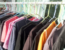 Clothes hanging. Colored clothing, Variety of casual shirts on wooden hangers Stock Photo