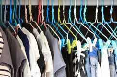 Clothes Hanging in Closet. By colorful wired hangers stock images
