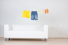 Clothes hanging over couch Stock Images