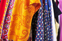 Clothes hanging on a rack in a flea market. Closeup of some used clothes hanging on a rack in a flea market royalty free stock images