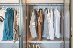 Clothes hanging on rail in modern wardrobe. Closet interior design stock image