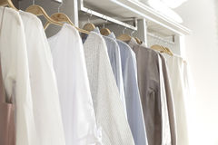 Clothes hanging on rail Stock Photos