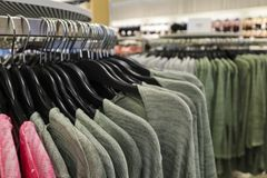 Clothes hanging in a row on store hangers stock photos
