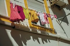 Clothes hanging on window drying in a colorful house. Close-up of clothes hanging on window drying in a colorful terraced house in a sunny day, in an alley of royalty free stock image