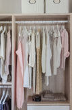 Clothes hanging in wooden wardrobe Royalty Free Stock Photos
