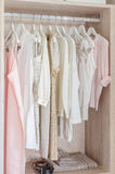 Clothes hanging in wooden wardrobe stock image