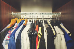 Clothes hanging in wooden wardrobe Royalty Free Stock Image