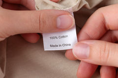 Clothes label. 100% cotton. Woman's hands holding clothes label. 100% cotton. Made in China Royalty Free Stock Image
