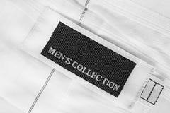 Lettered clothes label. Clothes label lettered men`s collection on white textile background Stock Photos