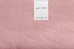 Clothes label says 100% cotton on pink textile background, close up stock images