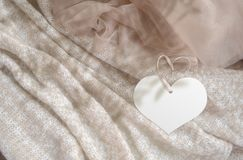 Clothes label tag on cloth background. Branding template mockup. Heart tag on light biege color stock photo