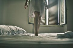 Clothes laid oLegs of a woman dressed in white standing on a white bed stock photo
