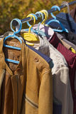 Clothes and leather jacket displayed at garage sale Stock Photos