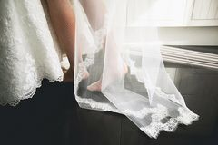 Clothes and legs of the bride close-up, against the black floor. A young woman takes a beautiful white openwork dress and a veil. royalty free stock images