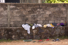 Clothes lying on wall. Closeup of different clothes on wall and ground outdoors royalty free stock images
