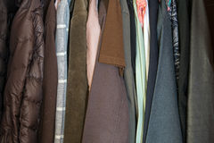 Clothes of many colors hanging in wardrobe Royalty Free Stock Photos