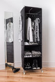 Clothes organizer with black and white clothing. Mobile clothes organizer with black and white clothing and shoes stock photography