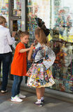 Clothes from paper. Vladivostok, Primorsky Region, Russia – September 27th, 2015: Vladivostok, the downtown, at a newsstand show-window one girl is interested Royalty Free Stock Photo