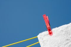 Clothes peg. On a white towel and washing line against a blue sky royalty free stock photos