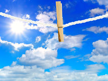 Clothes peg. Wooden clothes peg on line against blue cloudy sky with sun stock images