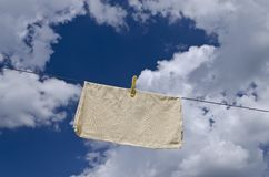 Clothes peg on a blue towel and washing line. Against a blue sky royalty free stock photos