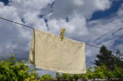 Clothes peg on a blue towel and washing line. Against a blue sky stock images