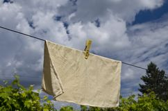 Clothes peg on a blue towel and washing line. Against a blue sky stock photos