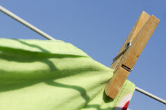 Clothes peg closeup. Clothes-peg holding a green table cloth royalty free stock photo