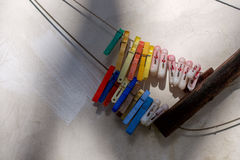 Clothes-peg in diffenetn color. Clothes-peg in different color on the wall stock image
