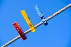 Clothes-peg over blue sky. Three, clothes-peg, over, blue, sky, clothes, rope, line, string, cord, object, red, yellow, everyday Royalty Free Stock Photography