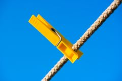 Clothes-peg over blue sky. Clothes-peg, over, blue, sky, clothes, rope, line, string, cord, object, yellow, everyday royalty free stock photos