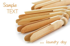 Clothes pegs. Old fashioned wooden clothespegs with selective focus on white background with room for text Royalty Free Stock Image