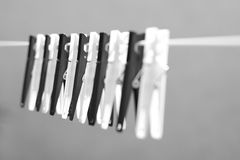 Clothes Pegs. A row of black and white clothes pegs on a line with a blue sky background Royalty Free Stock Image
